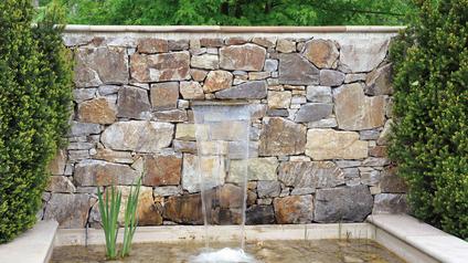 Bruchsteinmauer mit Edelstahl-Wasserspender.