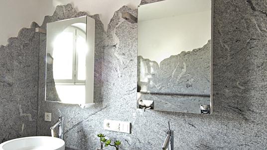 """Detailansicht: Wandverkleidung in Granit """"Viscont White""""; Kanten gesprengt und gebrochen."""