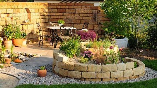 """Gartengestaltung mit Sandstein: Mediterane Mauer und """"Blumen-Kräuterschnecke"""""""