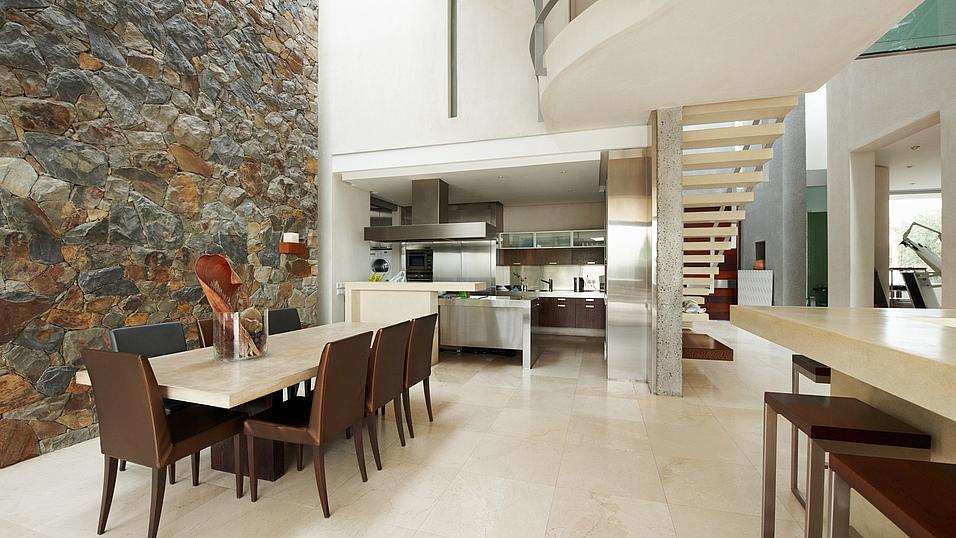 Moderne Küchengestaltung in Stein: Boden Tischplatte und Theke, beiger Marmor; Wand: Quarzit Bruchstein.