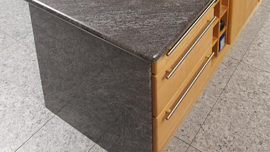 """Detailansicht: Arbeitsplatte mit abgerundeten Kanten und Seitenverkleidung in Granit """"Orion""""."""