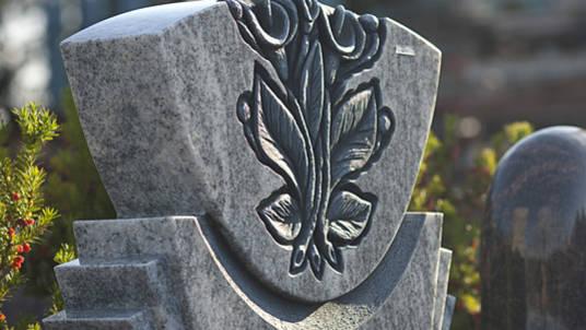 Granit Grabstein hell, mit floralem Ornament 'Calla'.