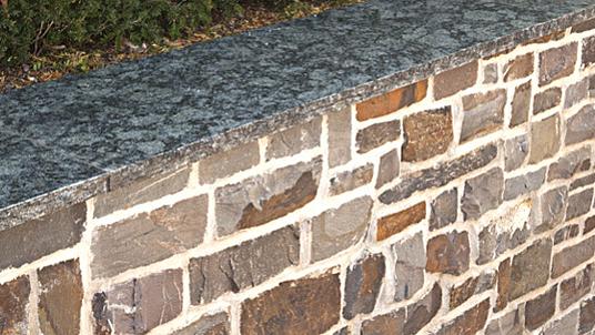 """Quarzit Bruchsteinmauer mit Granit Mauerabdeckung in """"Verde Olivo""""."""