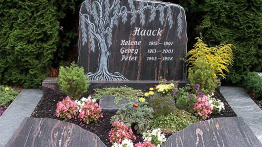 """Gedenkstein: Granit rot-grau mit Plastik """"Trauerweide""""."""