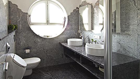 Waschtisch mit bodenfreiem Regal und massiven Badbodenfliesen in dunklem Granit.