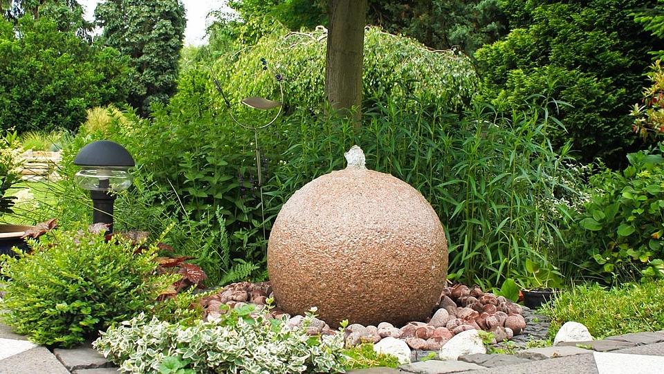 Runde Quellstein umrandet von rötlichen Kieseln, eingefasst von Kopfsteinpflaster