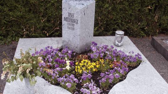 Grabstein aus hellem Granit mit Noten und Notenschlüssel.