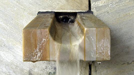 Edle Wasserrinne aus poliertem Marmor vor fein strukturierter Quarzitwand.