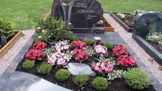 """Gedenkstätte in dunkelrotem und grauen Granit mit Bronzeplastik """"Lebensbaum""""."""