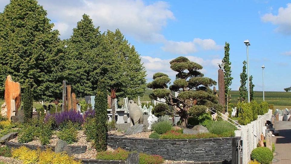 Gartengestaltung mit Natursteinen: Trockenmauern, Steinsitzmöbel, Feuerblumen, Gartenbrunnen und Findlinge.