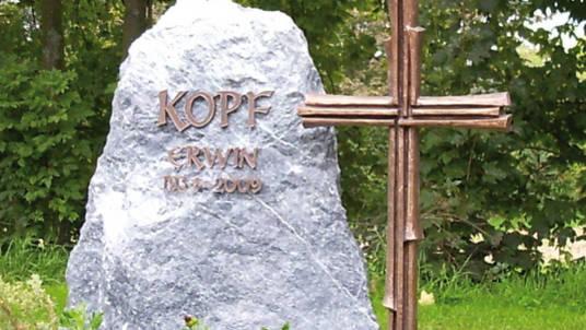 Naturstein: Fels kombiniert mit Kreuz aus Bronze.