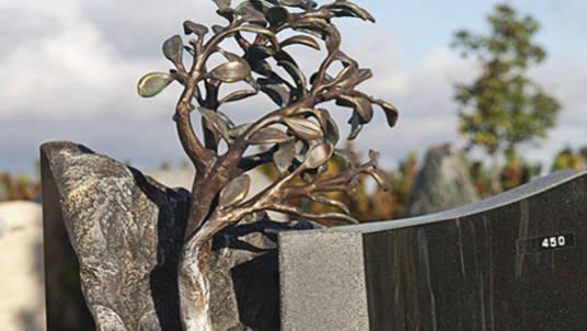 Dunkler Granit mit Bronzeskulptur 'Lebensbaum'.
